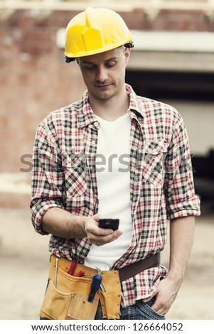 Construction worker reading a message on mobile phone - stock photo