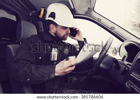 Construction worker reading papers, driving a car and talking on the phone while drinking coffee in Finland. He is wearing a white helmet and he has a dirty overalls. Image includes a vintage effect. - stock photo