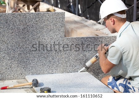 Construction worker sealing joints between ceramic Tiles - stock photo