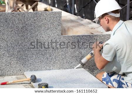 Construction worker sealing joints between ceramic Tiles - stock photo