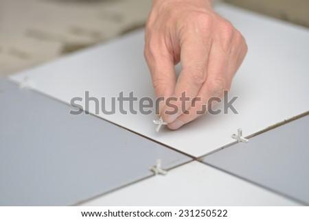 Construction worker set up spacers between tiles on a floor - stock photo