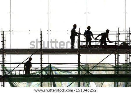 Construction worker silhouette at work  - stock photo