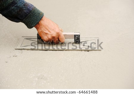 Construction worker spreading wet concrete, background copy-space - stock photo
