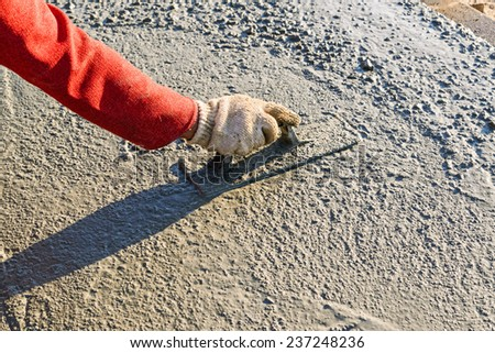 Construction worker spreading wet poured concrete  - stock photo