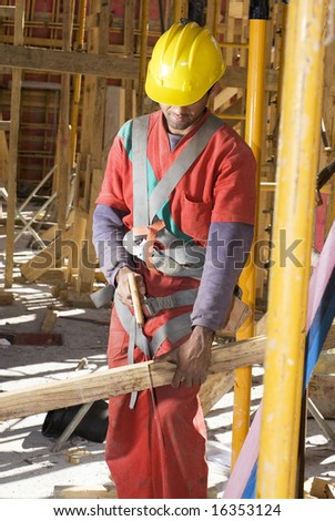 Construction worker stands while holding board. He is cutting it with a hand saw. Vertically framed photo.