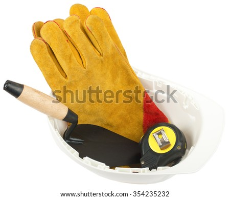 Construction worker supplies including hard hat and gloves on isolated white background - stock photo