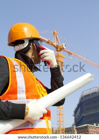 construction worker talking in mobile phone. Wearing orange safety vest and looking yellow crane on the background - stock photo