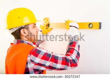 Construction worker using a water level