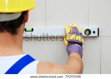 Construction worker using level.