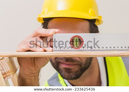 Construction worker using spirit level in a new house - stock photo