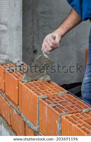 Construction worker using trowel on a hollow clay block wall. Brick trowel and clay blocks. Selective focus.  - stock photo
