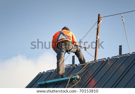 Construction worker wearing safety harness and safety line working on a pitched roof - stock photo