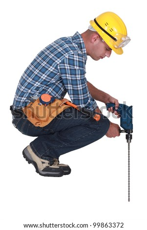 Construction worker with a masonry drill - stock photo