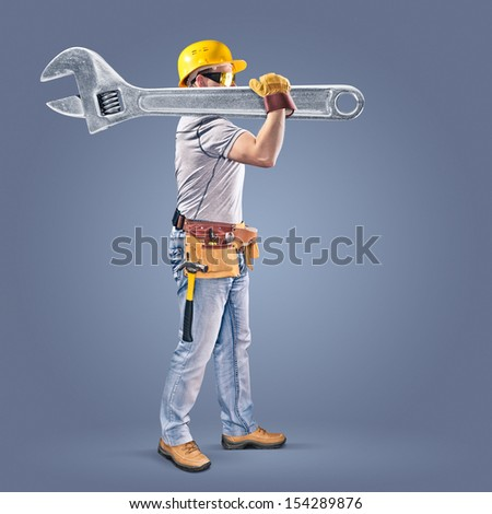construction worker with a tool belt and a wrench - stock photo