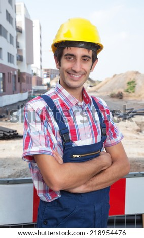 Construction worker with black hair and crossed arms - stock photo