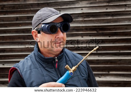 Construction worker with goggles and gas burner - stock photo