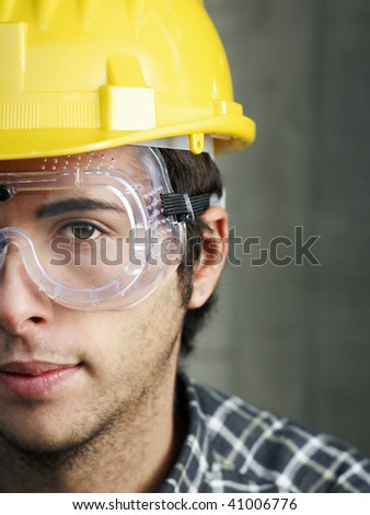 Construction worker with goggles looking at camera. Copy space - stock photo