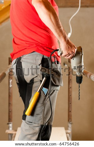 construction worker with hand drill standing on a scaffold - stock photo