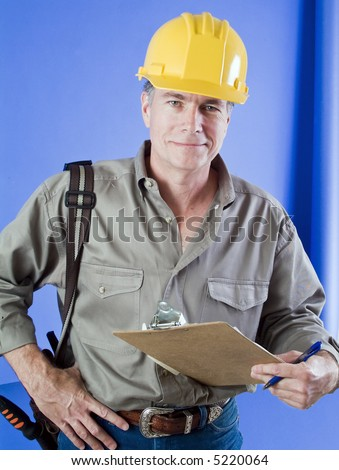 Construction worker with hard hat and clip board standing in front of a bright blue wall. - stock photo