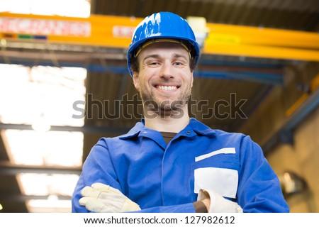 Construction worker with helmet posing in front of crane - stock photo