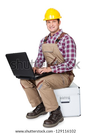 Construction worker with laptop. Isolated on white background - stock photo