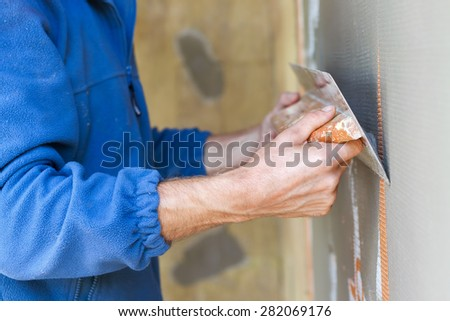 Construction worker with long trowel plastering a wall - stock photo