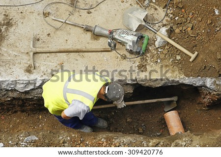 construction worker with pneumatic hammer drill , pick and shovel to repair  water and sewer pipes - stock photo