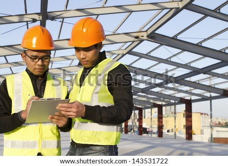 construction  worker with safety vest under new building - stock photo
