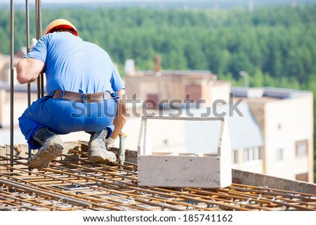 Construction worker with tool box mounting form work during concreting building floors - stock photo