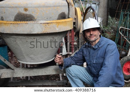Construction Worker with trowel and cement mixer - stock photo