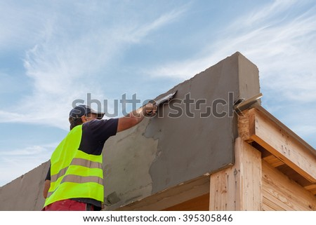 Construction worker with trowel plastering a facade of a new house - stock photo