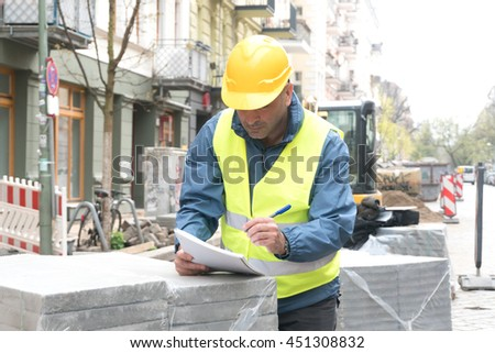 Construction worker with yellow helmet and safety vest taking notes