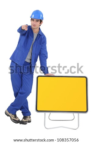 Construction worker with yellow road sign - stock photo