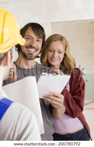 Construction worker young couple holding paper smiling - stock photo