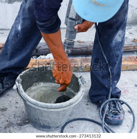 Construction workers are mixing cement with the trowel and power drill ingredients blended together better and ready to be plastered facades in construction next step.   - stock photo
