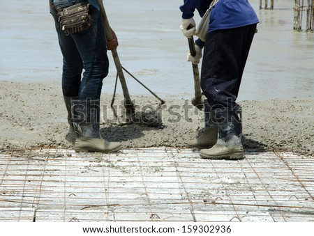 Construction workers are using the newly poured cement spreaders of crane into the ground to allow ordinary cement concrete with a thickness determined by the engineer and a smooth uniform surface. - stock photo