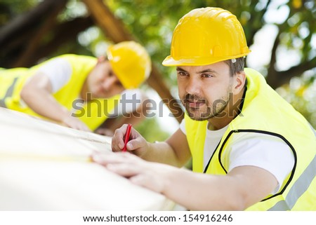 Construction workers collaborating on new house building - stock photo