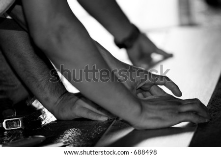 Construction workers helping each other during a remodel and/or floor installation - black and white image. - stock photo