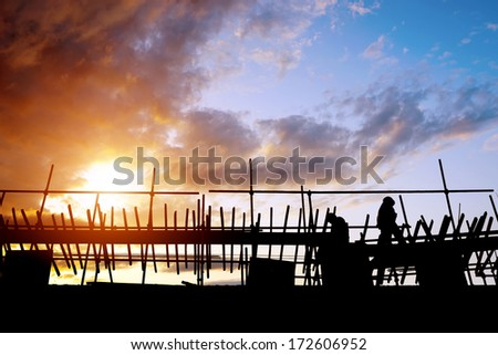 construction workers in the sunset - stock photo