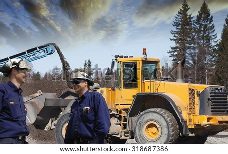 construction workers, machines and building site - stock photo