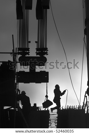 Construction workers outdoors back lit by the setting sun. - stock photo