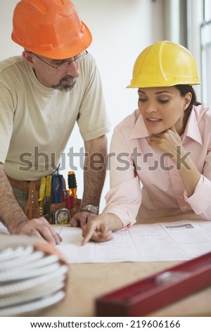 Construction workers reading blue prints
