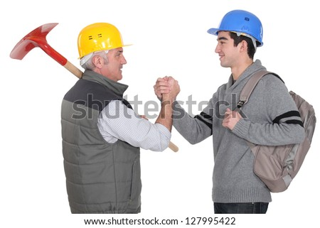 Construction workers shaking hands - stock photo