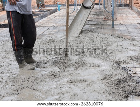 Construction workers spreading freshly poured concrete mix for house building - stock photo