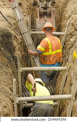 Construction workers using trench shoring equipment to backfill and install deep utilities at a new commercial  development - stock photo