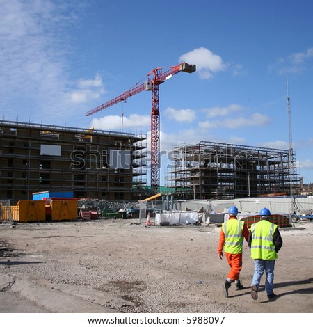 construction workers walking near building site with crane - stock photo