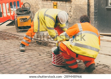 Construction workers wearing protective gear - Concept of road repairs - stock photo