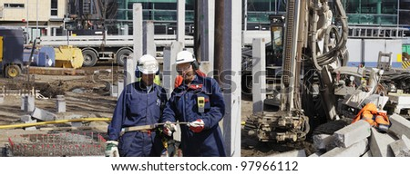 construction workers with engineering geodesy machine in background, panoramic view - stock photo