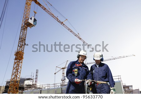 construction workers with giant cranes, scaffolding and machinery,  background slightly blurred