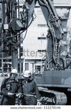 construction workers with giant heavy ground machines